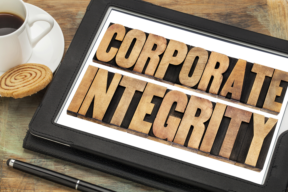 corporate integrity - business ethics concept - text in letterpress wood type on digital tablet computer with stylus pen, coffee cup and cookie