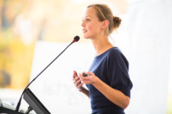 young business woman giving a presentation in a conference/meeting setting